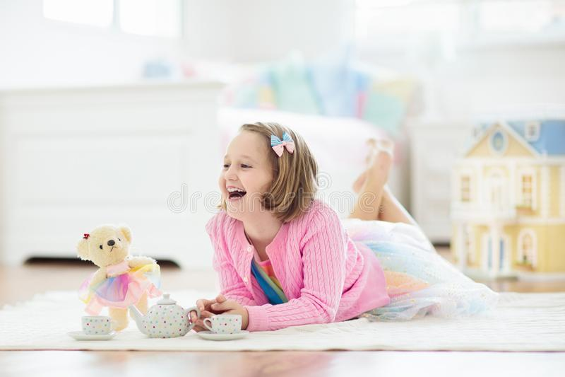 Liten flicka som spelar med dockhuset Unge med leksaker royaltyfri fotografi