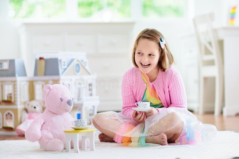Liten flicka som spelar med dockhuset Unge med leksaker royaltyfri bild