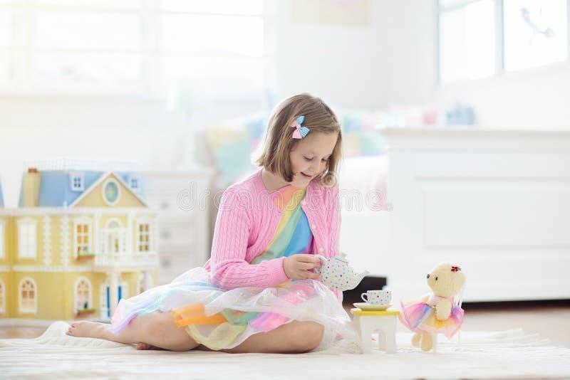 Liten flicka som spelar med dockhuset Unge med leksaker arkivfoto