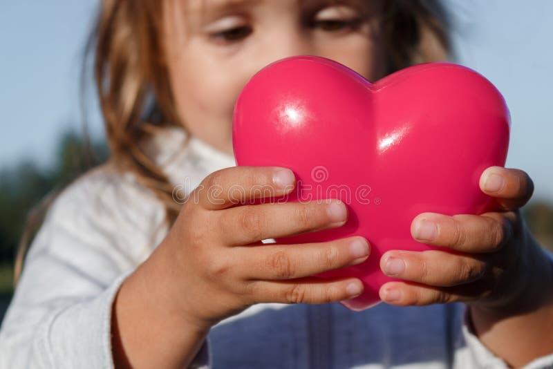 Liten flicka som spelar med en röd plast- hjärta hon rymmer det i henne händer fotografering för bildbyråer