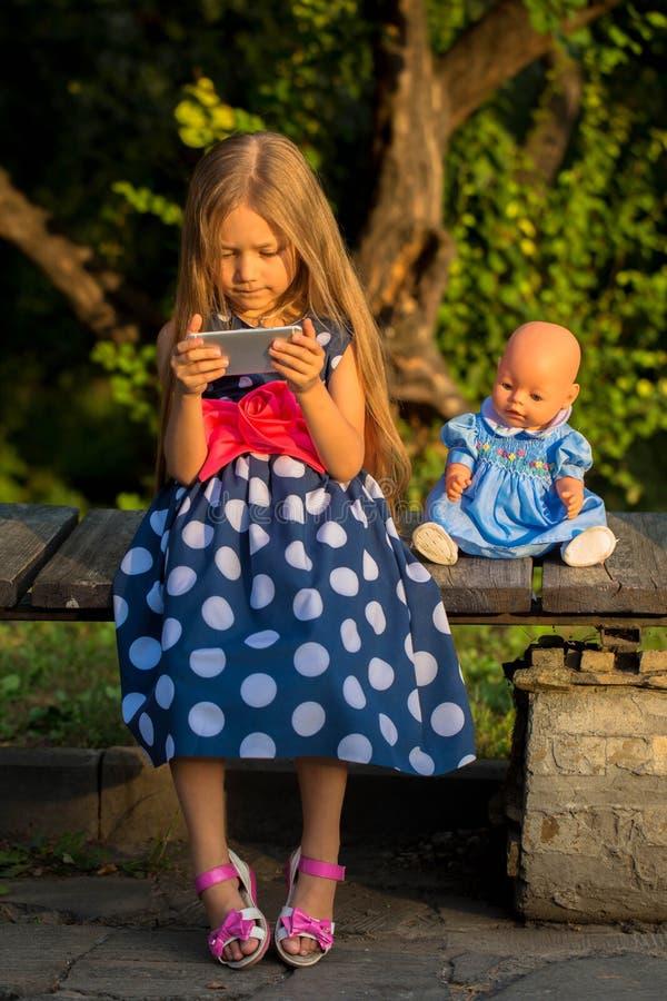 Liten flicka som spelar med en smartphone utomhus royaltyfri bild