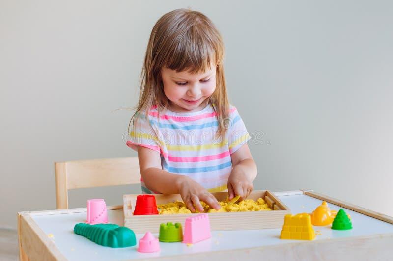 Liten flicka som spelar med färgrik kinetisk sand arkivbild