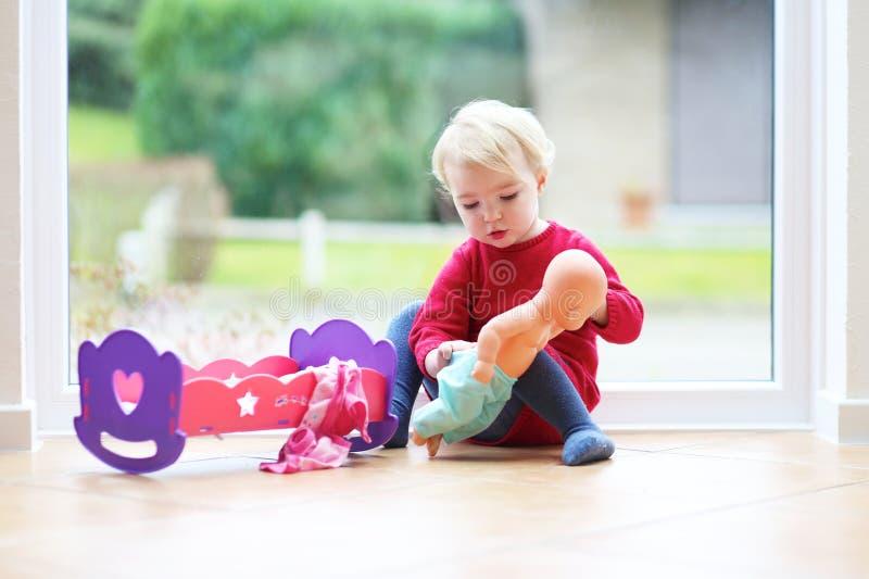 Liten flicka som spelar med hennes docka arkivfoton