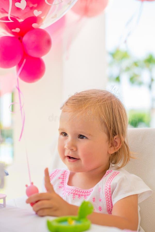 Liten flicka som spelar med hennes födelsedaggåva royaltyfria bilder