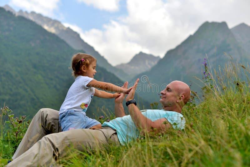 Liten flicka som spelar med hennes farsa på det gröna gräset arkivfoton