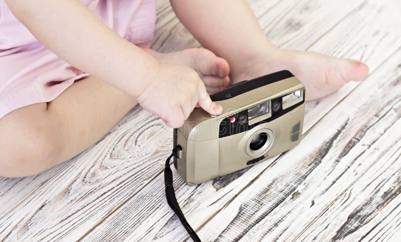 Liten flicka som spelar med kameran, liten närbild fotografering för bildbyråer