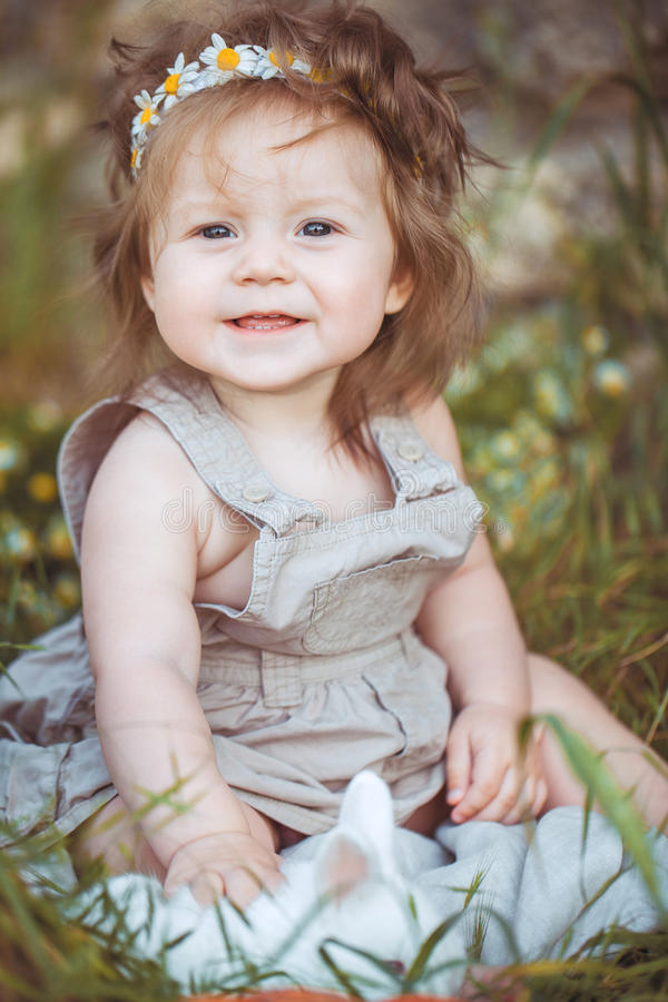 Liten flicka som spelar med kanin i byn. Utomhus-. Sommarstående. arkivfoto