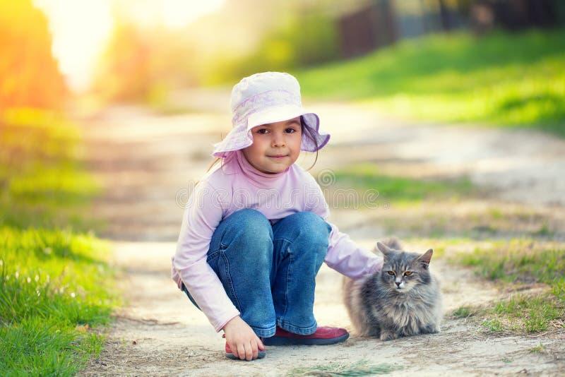 Liten flicka som spelar med katten royaltyfria foton