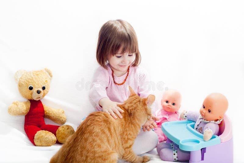Liten flicka som spelar med katten royaltyfri bild