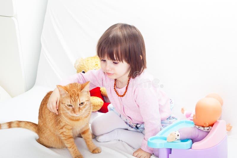 Liten flicka som spelar med katten royaltyfria bilder