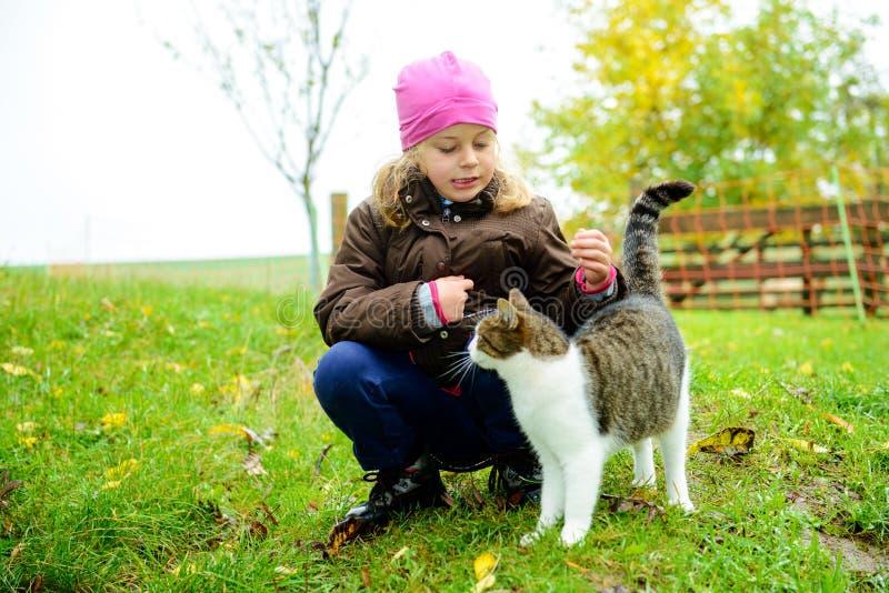 Liten flicka som spelar med katten arkivbilder