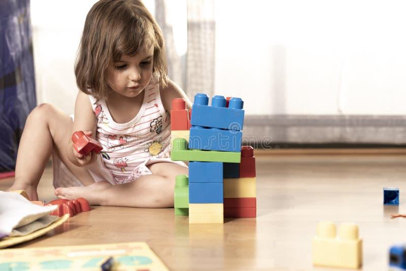 Liten flicka som spelar med kvarterleksaker royaltyfri bild