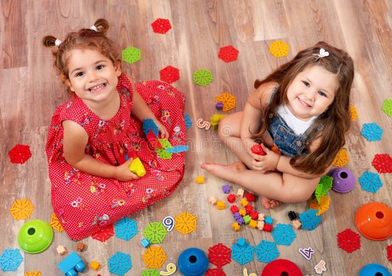 Liten flicka som spelar med kvarterleksaker Toys f?r ungar royaltyfri bild