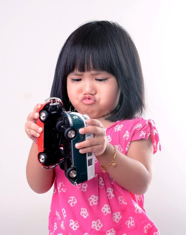 Liten flicka som spelar med leksakbilar royaltyfria foton