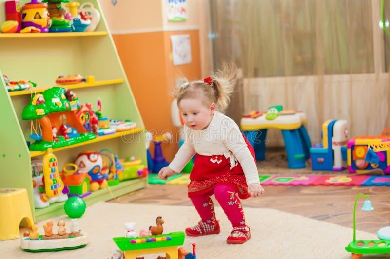Liten flicka som spelar med leksaker i lekrum arkivbild