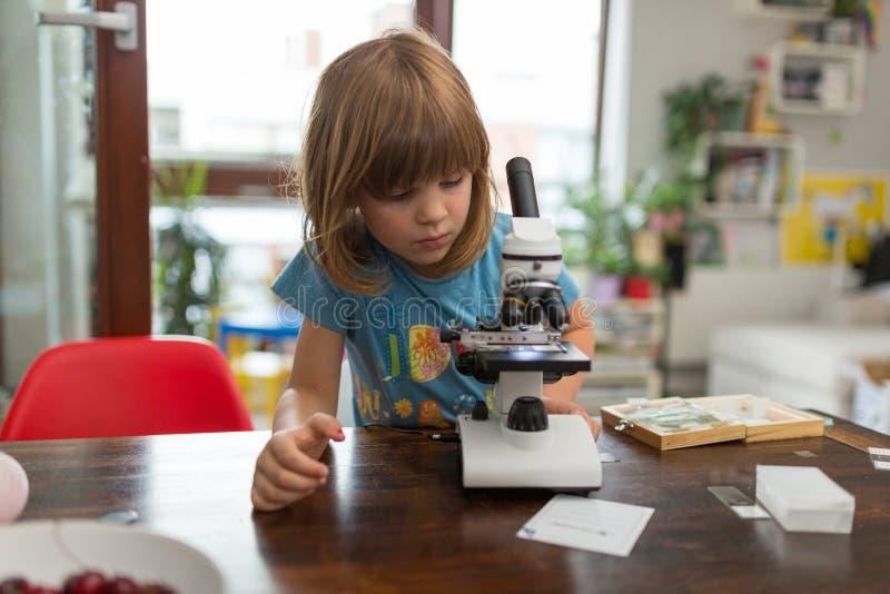 Liten flicka som spelar med mikroskopet royaltyfria bilder