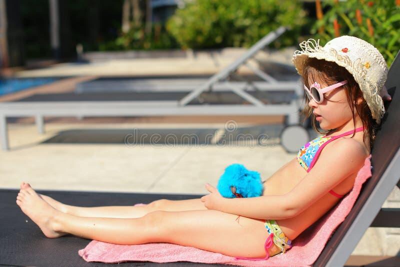 Liten flicka som spelar med minnestavlan nära simbassäng royaltyfri fotografi