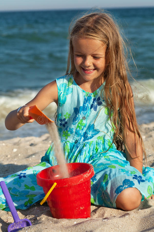 Liten flicka som spelar med sand på stranden royaltyfria foton
