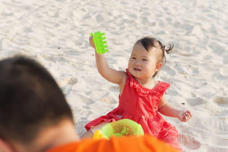 Liten flicka som spelar med sand p? stranden arkivbilder