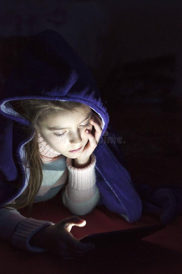 Liten flicka som spelar minnestavlaPC i sovrum på natten, fotografering för bildbyråer