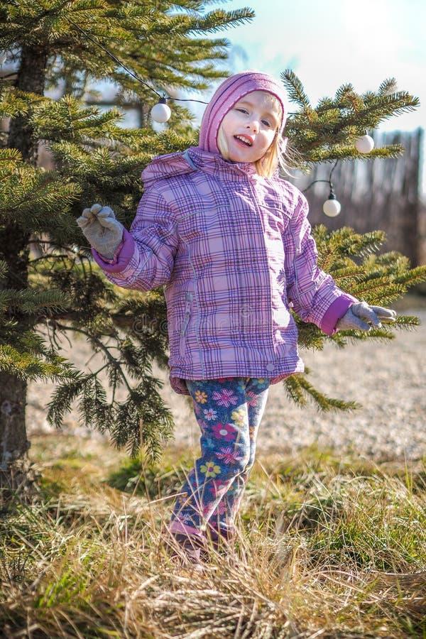Liten flicka som spelar nära ett dekorerat stiftträd royaltyfria foton
