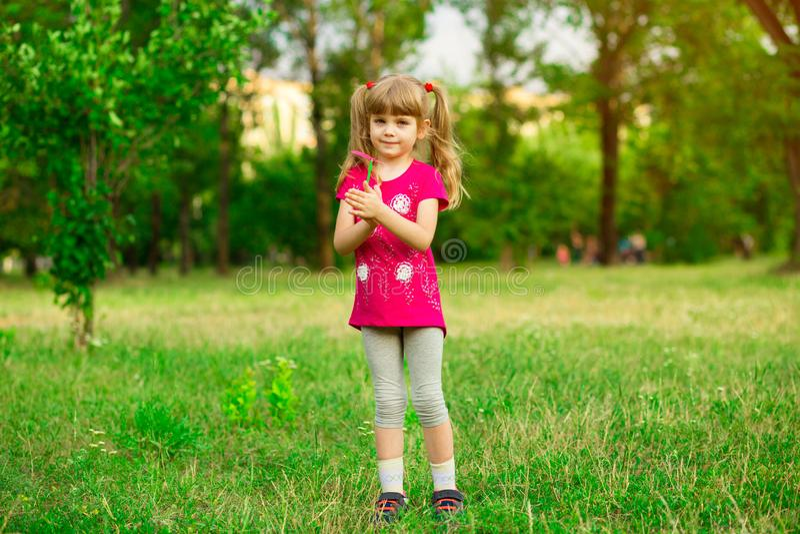 Liten flicka som spelar p? ?ngen p? solen med v?derkvarnen i hennes h?nder Barn som rymmer vindleksaken royaltyfria bilder