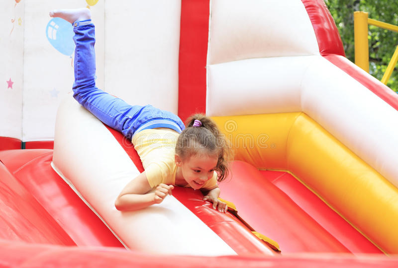 Liten flicka som spelar på en trampolin. fotografering för bildbyråer