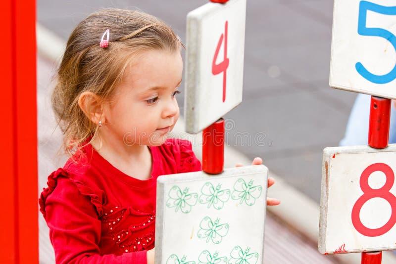Liten flicka som spelar på lekplatsen royaltyfri bild