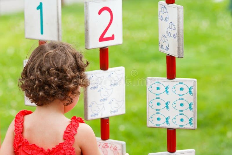 Liten flicka som spelar på lekplatsen fotografering för bildbyråer