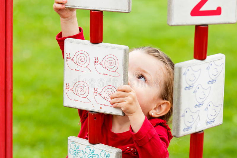 Liten flicka som spelar på lekplatsen arkivfoto