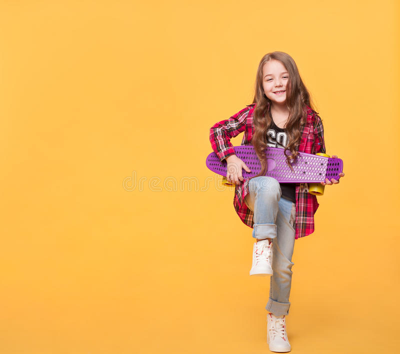 Liten flicka som spelar på skateboarden på gul bakgrund royaltyfri bild