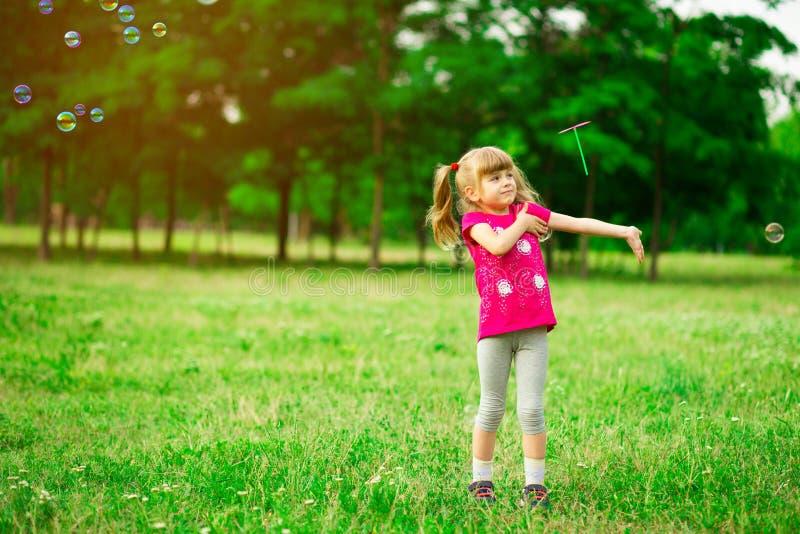 Liten flicka som spelar p? ?ngen p? solen med v?derkvarnen i hennes h?nder Barn som rymmer vindleksaken royaltyfri fotografi