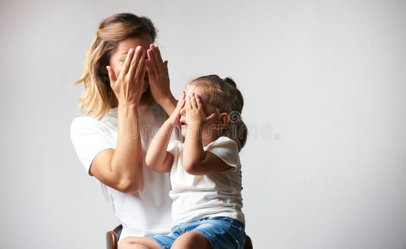 Liten flicka som spelar peekabooleken med hennes moder arkivbilder