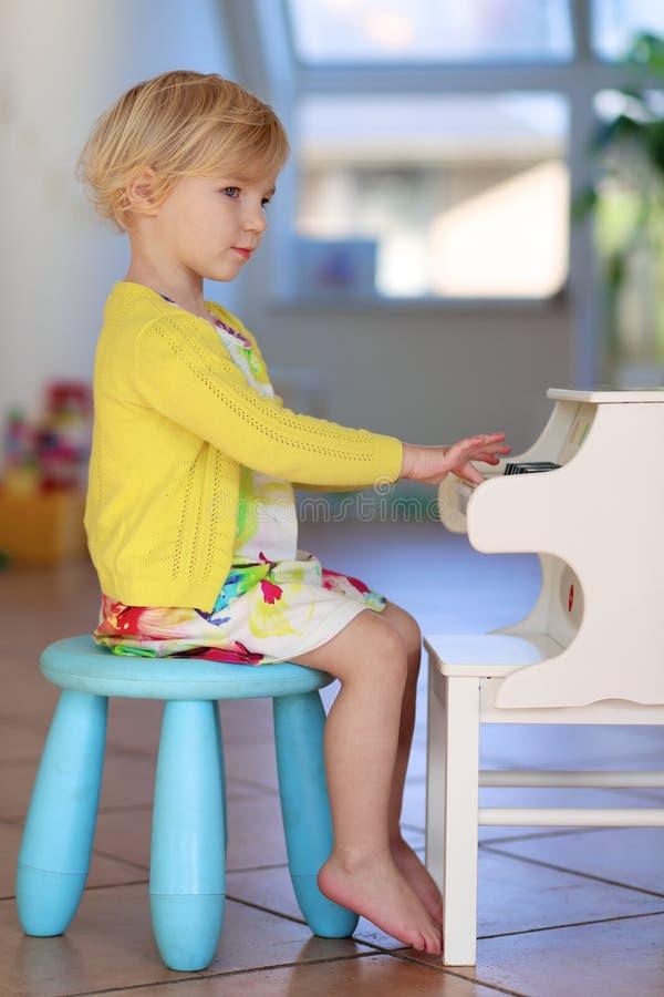 Liten flicka som spelar pianot inomhus fotografering för bildbyråer