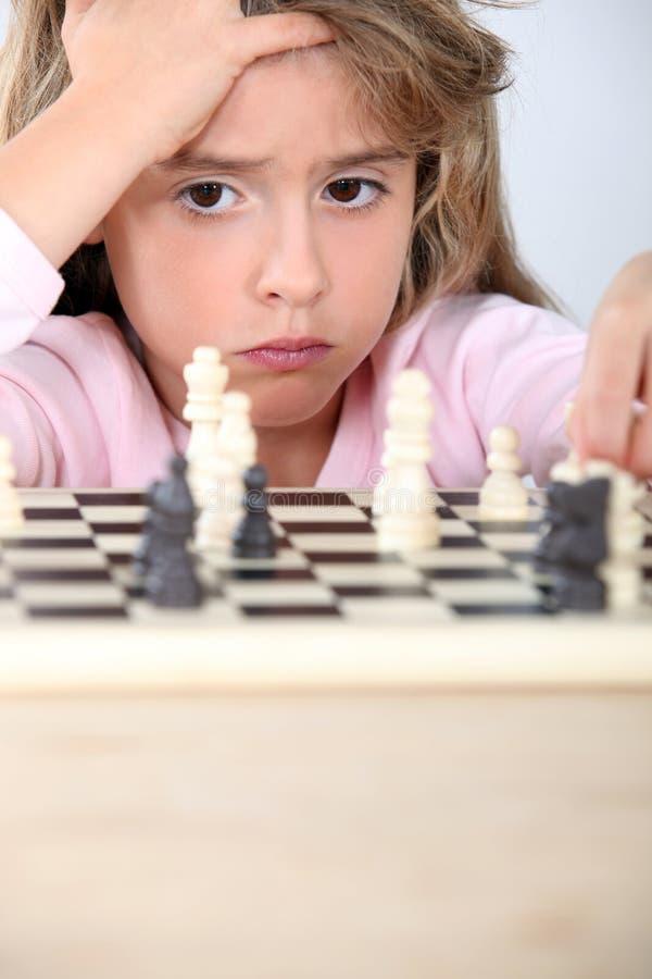Liten flicka som spelar schack royaltyfri fotografi