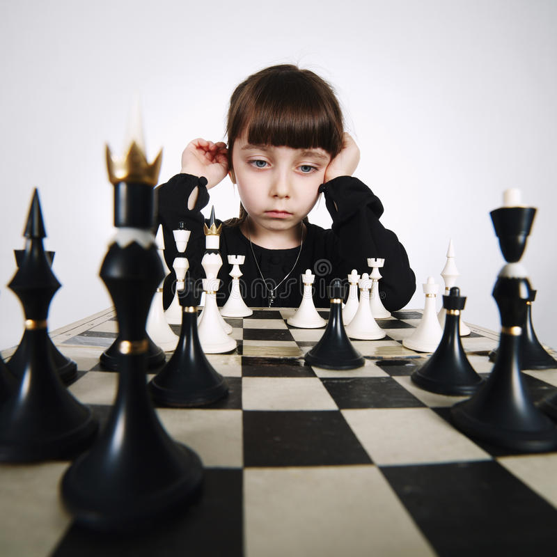 Liten flicka som spelar schack på vit arkivfoton