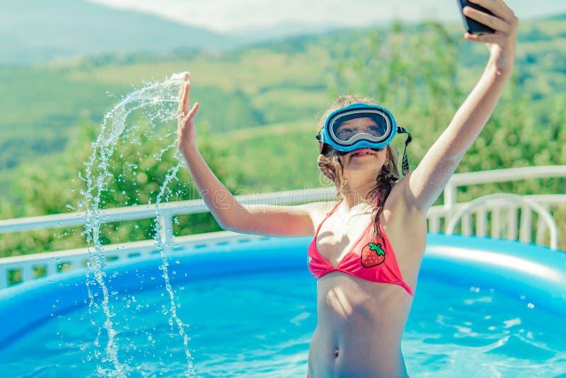 Liten flicka som spelar simbassängen och att göra selfie med telefonen för sociala nätverk arkivbilder