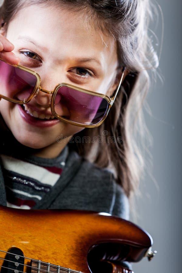 Liten flicka som spelar som en rockstar gitarrhjälte arkivbilder