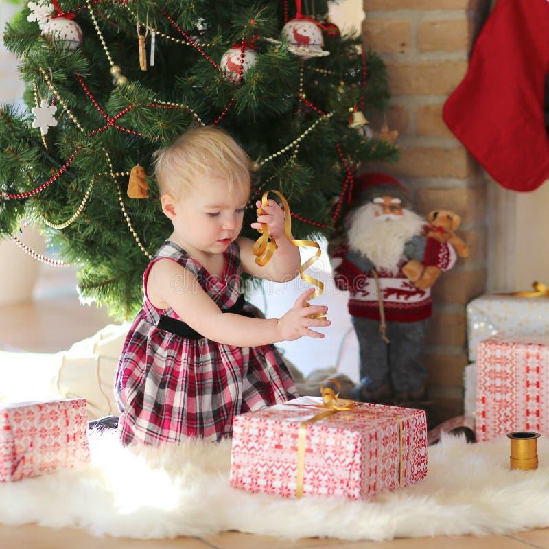 Liten flicka som spelar under julträd på solig vinterdag arkivbild