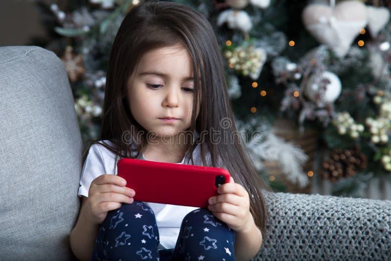 Liten flicka som spelar vid julgranen arkivbilder