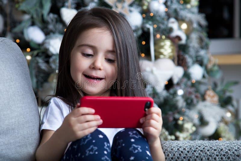Liten flicka som spelar vid julgranen royaltyfri bild