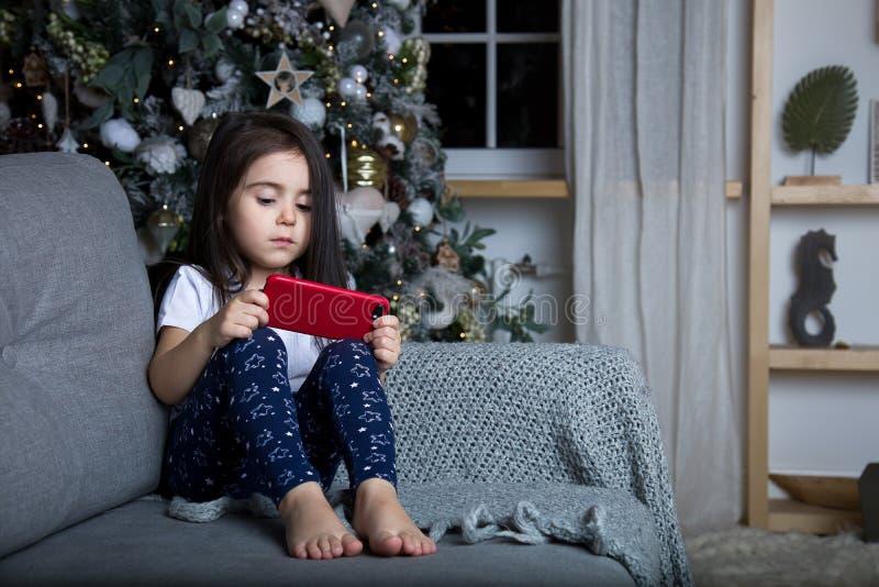 Liten flicka som spelar vid julgranen arkivfoton