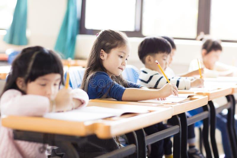 Liten flicka som studerar i klassrumet arkivbild