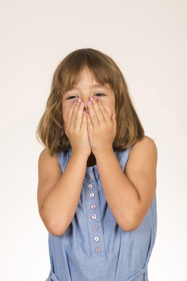Liten flicka som täcker hennes framsida med händer fotografering för bildbyråer