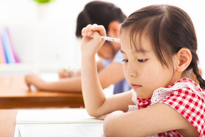 Liten flicka som tänker i klassrumet royaltyfri bild