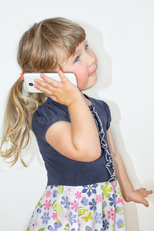 Liten flicka som talar på en mobiltelefon, på en vit bakgrund royaltyfri foto