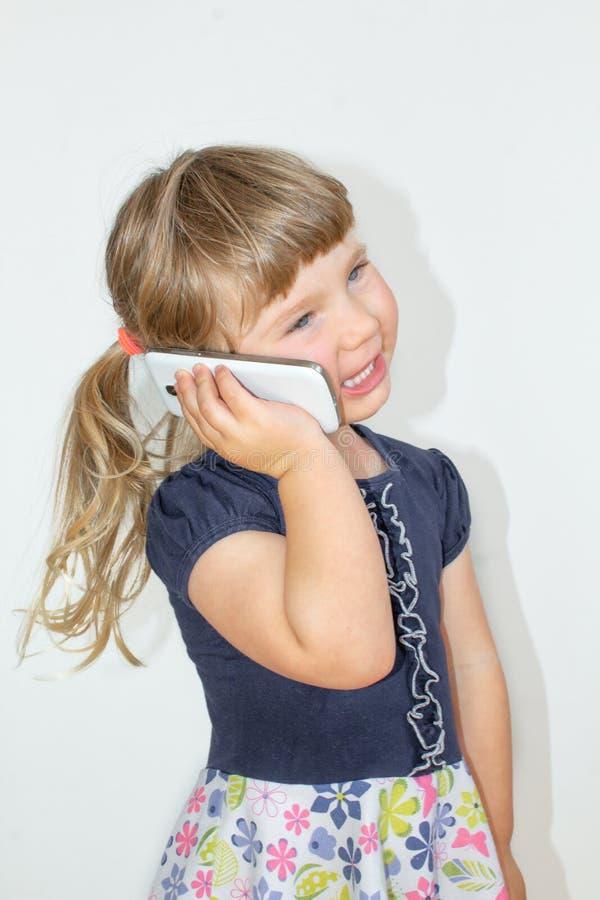 Liten flicka som talar på en mobiltelefon, på en vit bakgrund royaltyfria foton