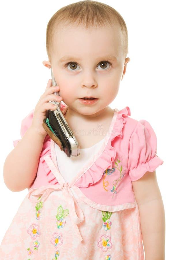 Liten flicka som talar på telefonen i en rosa klänning royaltyfria bilder