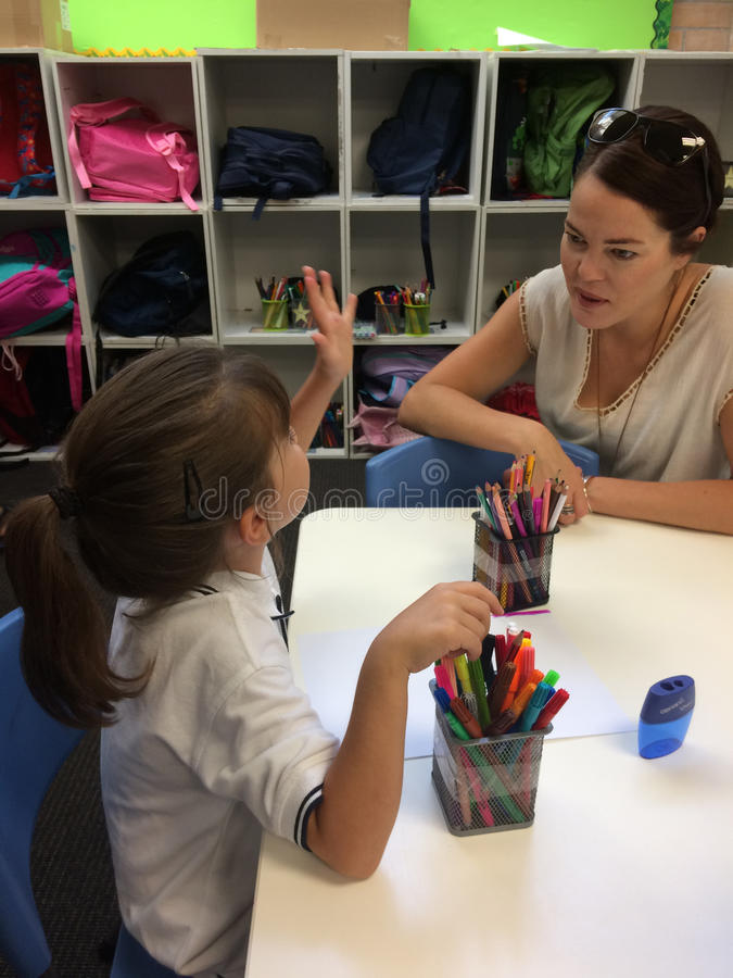 Liten flicka som talar till hennes lärare arkivbilder