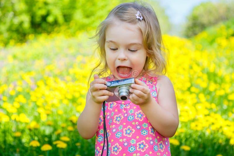 Liten flicka som tar bilder på en äng royaltyfri fotografi